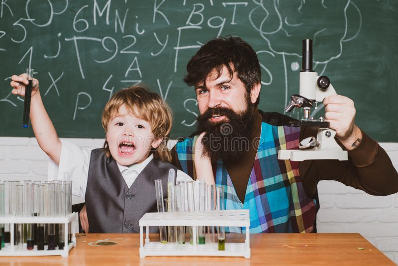 Back to school. Elementary school teacher and student in classroom. Home schooling. Father teaching her son chemistry or royalty free stock photos