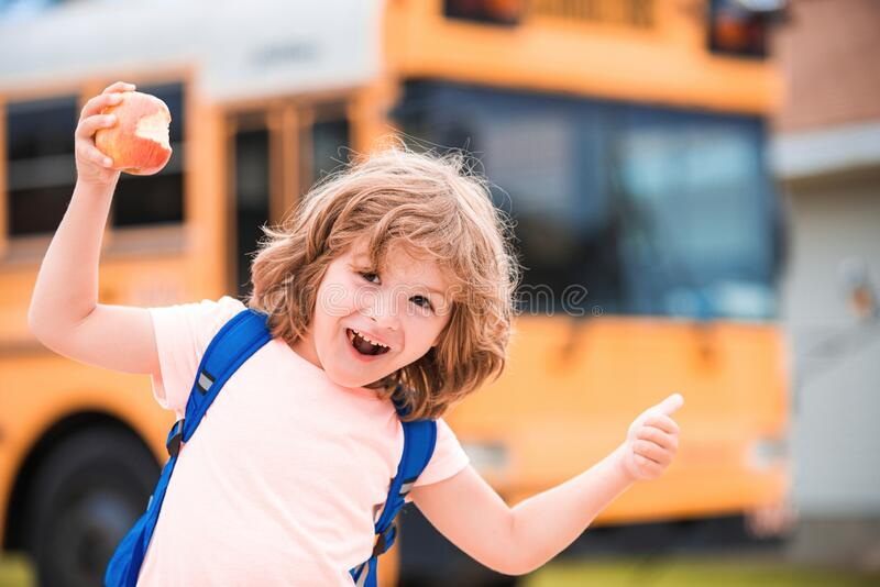 Back to school. Excited school boy on school bus. Child with positive gesture with hand, thumbs up smiling and happy stock photo