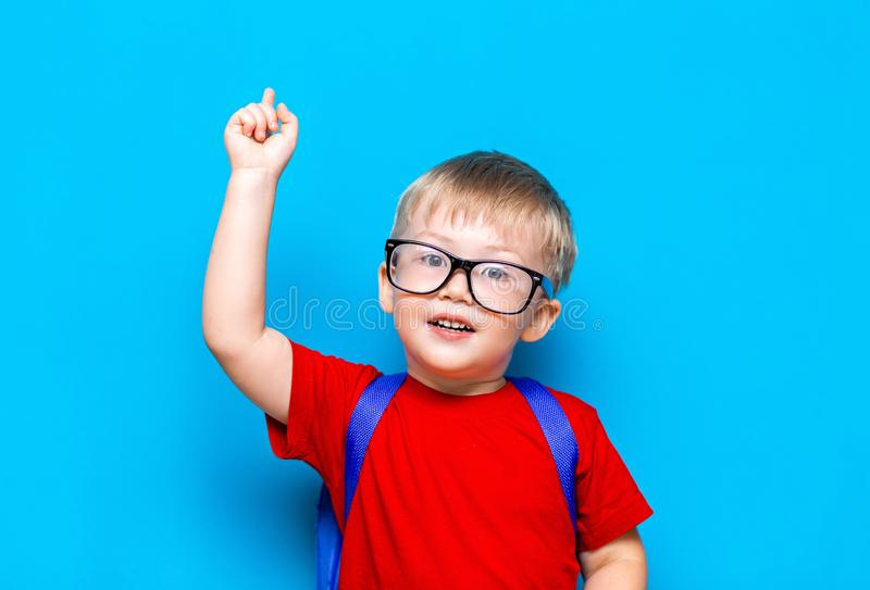 Back to school First grade junior lifestyle. Small boy in red t-shirt. Close up studio photo portrait of smiling boy in glasses royalty free stock images
