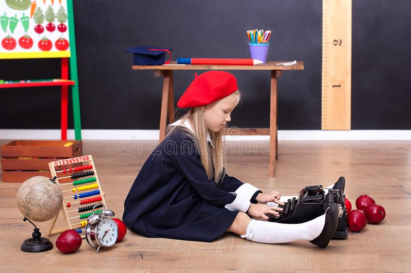 Back to school! A girl sits on the floor at school and holds a retro typewriter. School education. Little writer, journalist. The royalty free stock photo