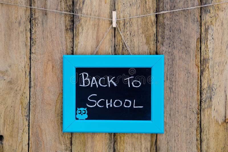 Back to School hand written in chalk on blackboard with blue frame hanging against rustic timber wooden background - with owl. Back to School hand written in stock image