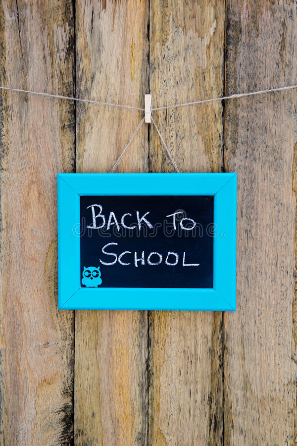 Back to School hand written in chalk on blackboard with blue frame hanging against rustic timber wooden background - with owl. Back to School hand written in royalty free stock images