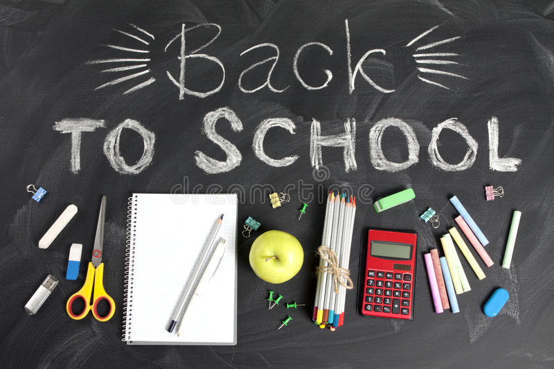 `Back to school` handwritten with school supplies on a black background. Top view. `Back to school` handwritten with school supplies on a black background. Top royalty free stock photos