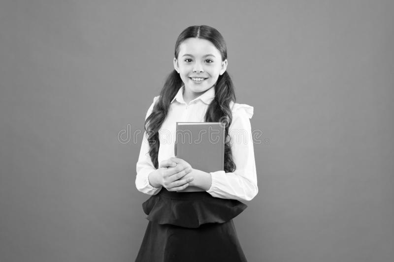 Back to school. happy child. reading lesson. Book store concept. small girl in school uniform. schoolgirl writing notes. On orange background. get information royalty free stock images