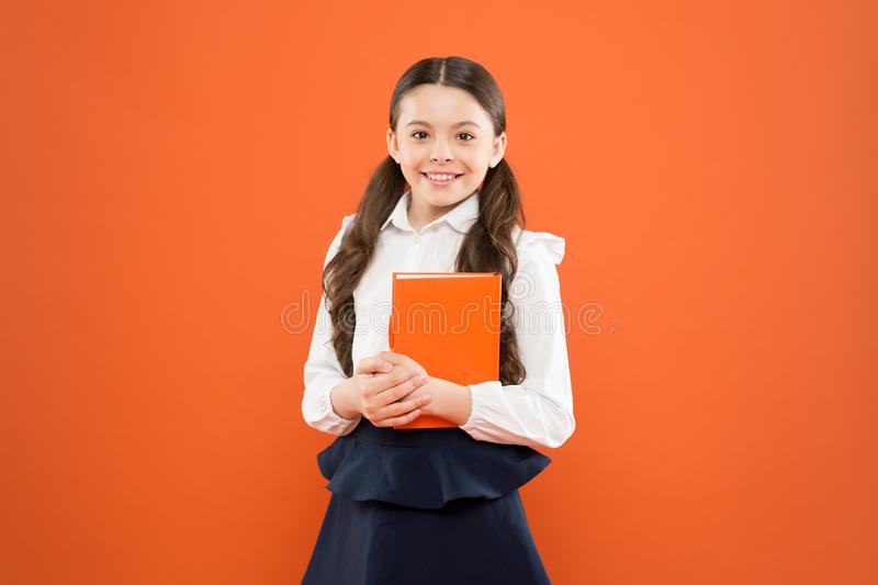 Back to school. happy child. reading lesson. Book store concept. small girl in school uniform. schoolgirl writing notes. On orange background. get information royalty free stock photos
