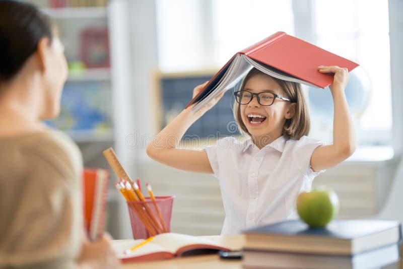 Girl with teacher in classroom stock photo