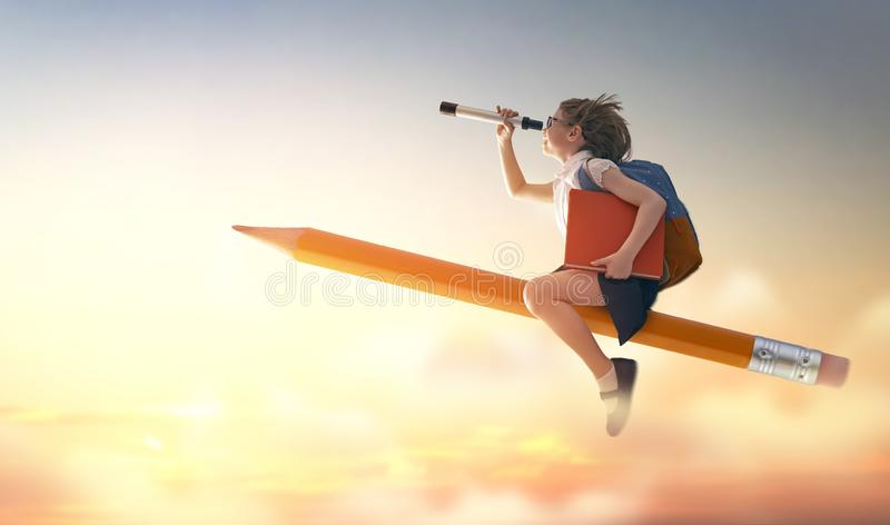 Child flying on a pencil. Back to school! Happy cute industrious child flying on the pencil on background of sunset sky. Concept of education and reading. The royalty free stock photos