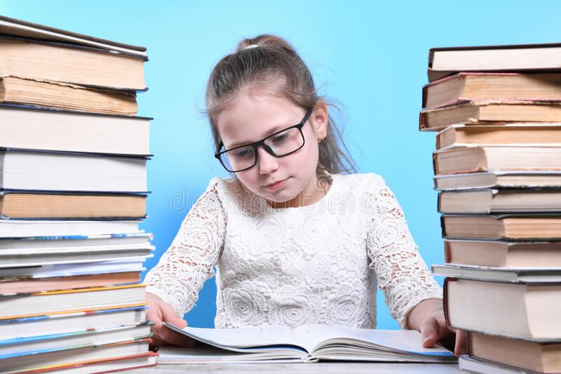 Back to school .Happy cute industrious child is sitting at a desk indoors. Kid is learning in class.Mountains of books on the. Back to school Happy cute royalty free stock photo