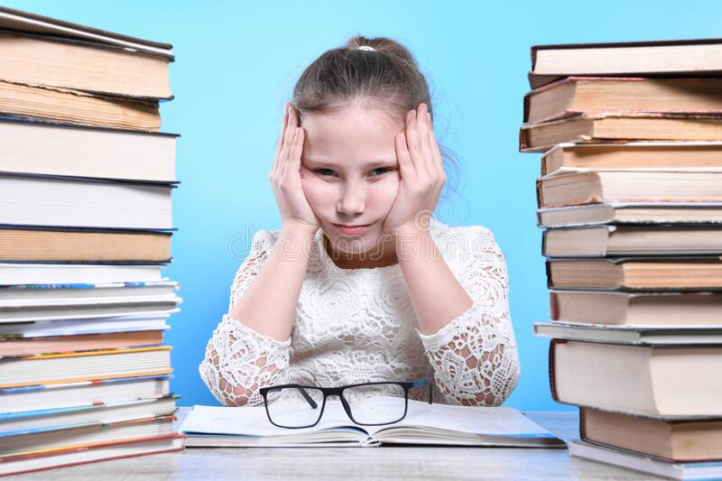 Back to school .Happy cute industrious child is sitting at a desk indoors. Kid is learning in class.Mountains of books on the. Back to school Happy cute royalty free stock photos