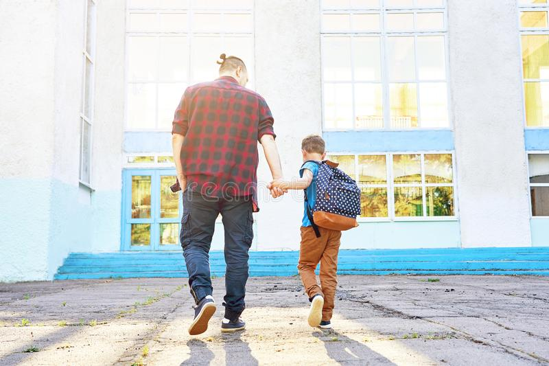Back to school. Happy father and son go to elementary school stock photos