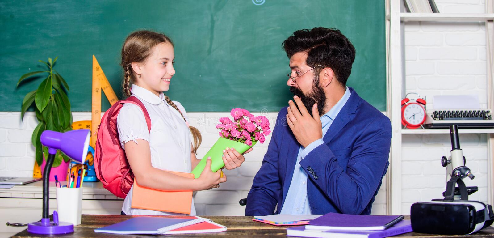 Back to school. Happy teachers day. small school girl kid with flower bouquet. flower present for best teacher royalty free stock photo