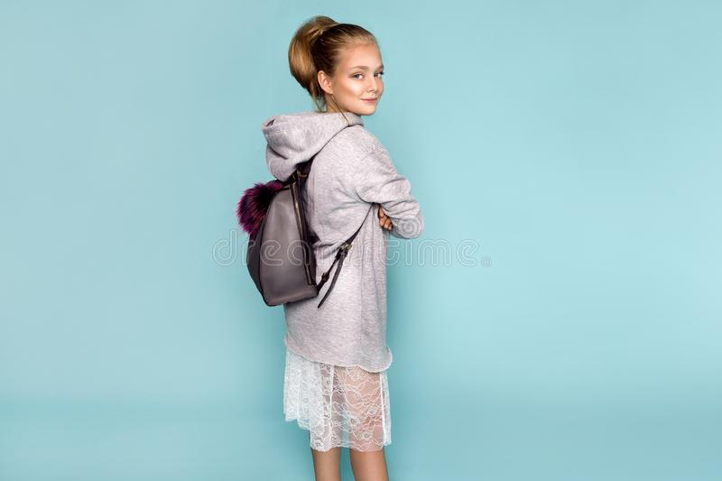 Back to school and happy time! Cute industrious child is breaking through color paper wall. Kid with backpack. Girl ready to study stock photography