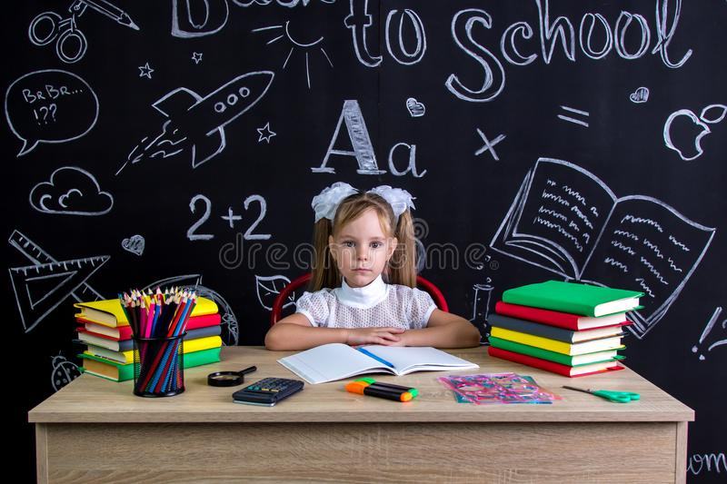 Back to school and happy time. Cute industrious child is sitting at a desk indoors with books, school supplies. Girl royalty free stock photo