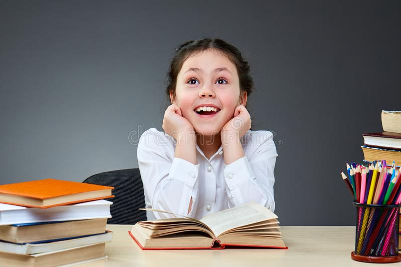 Cute industrious child is sitting at a desk indoors. Kid is learning in class on background of blackboard. Back to school and happy time. Cute industrious child royalty free stock photo