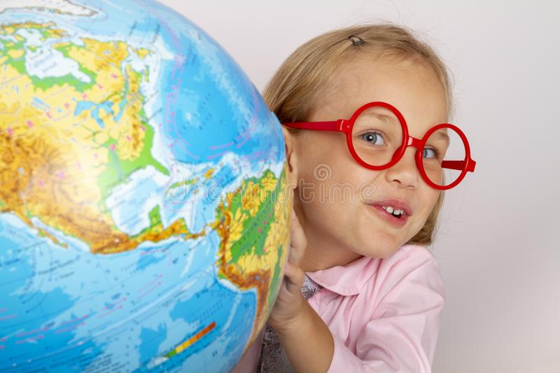 Cute industrious child is sitting at a desk indoors. stock photo