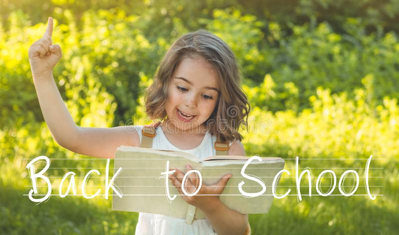 Back to school and happy time! Cute industrious child is standing with a book and a briefcase royalty free stock images