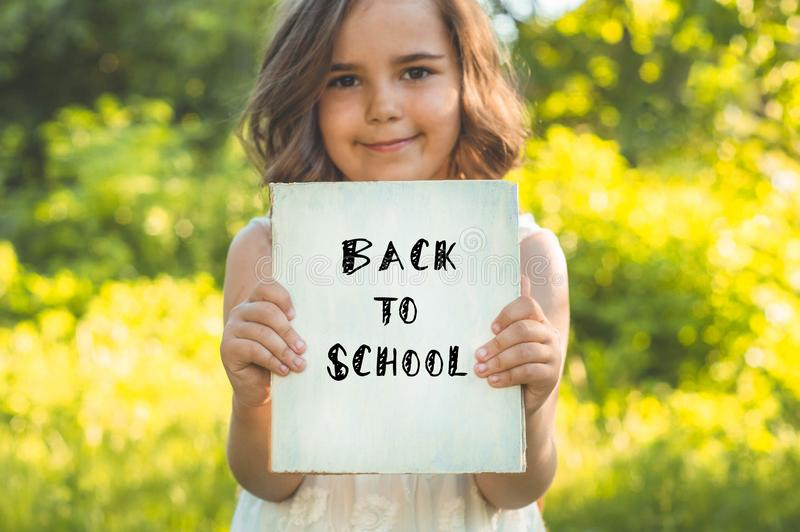 Back to school and happy time! Cute industrious child is standing with a book and a briefcase stock photography
