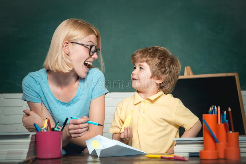 Back to school and happy time. Funny little child and young female teacher having fun on blackboard background. Teachers royalty free stock photo