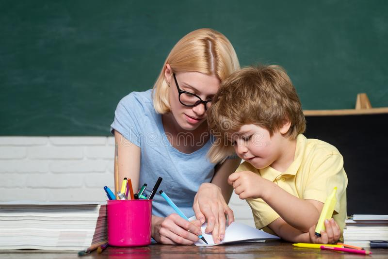 Back to school and happy time. Teacher helping kids with their homework in classroom at school. Talented child royalty free stock images
