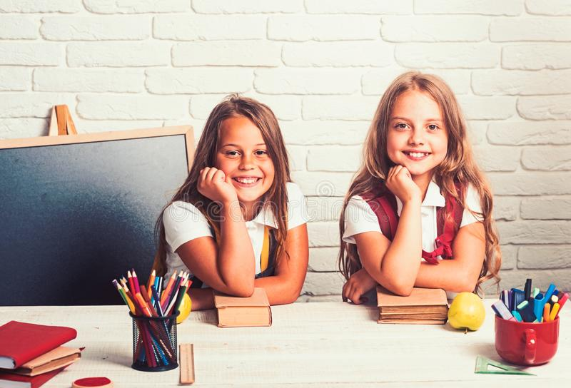 Back to school and home schooling. Happy school kids at lesson in september 1. Little girls eat apple at lunch break stock photography