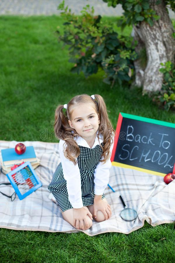 Back to school. The kid is ready for school. smart child a little girl with school supplies sits on a lawn: a school board, books, royalty free stock photography