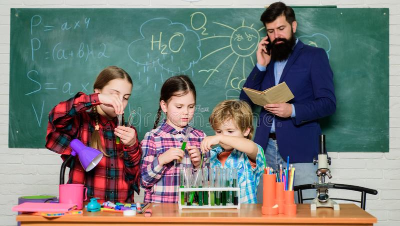 Back to school. kids in lab coat learning chemistry in school laboratory. chemistry lab. making experiment in lab or. Chemical cabinet. happy children teacher stock image