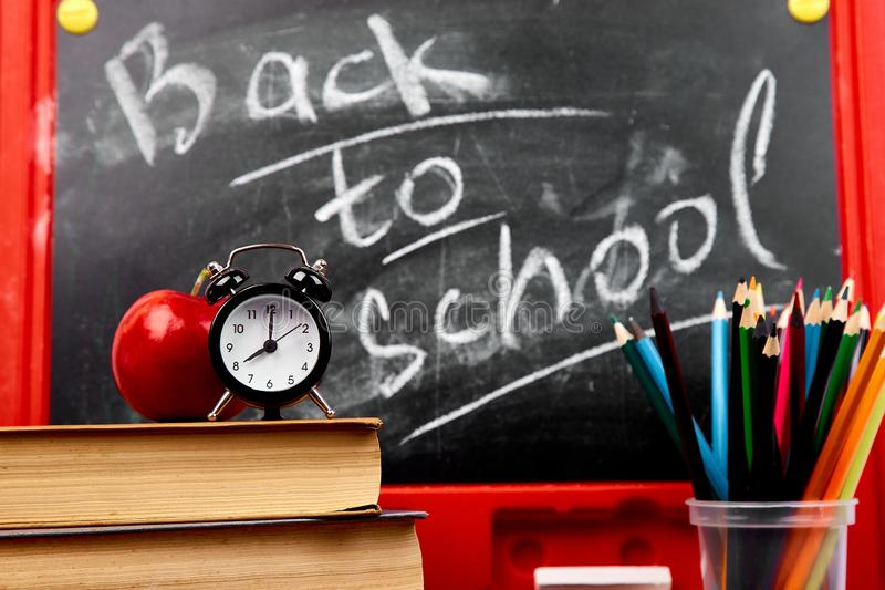Back to school lettering on blackboard with piece of chalk stock image