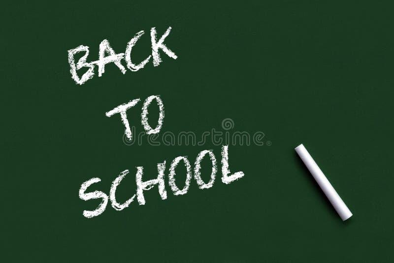 Back to school lettering over green chalkboard black background stock images