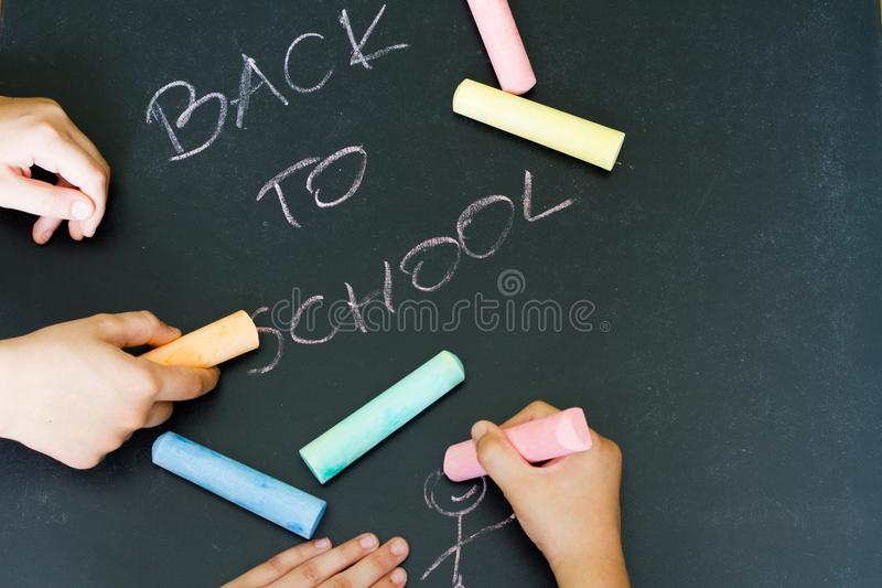 Back to school letters and drawing kids on blackboard royalty free stock photos