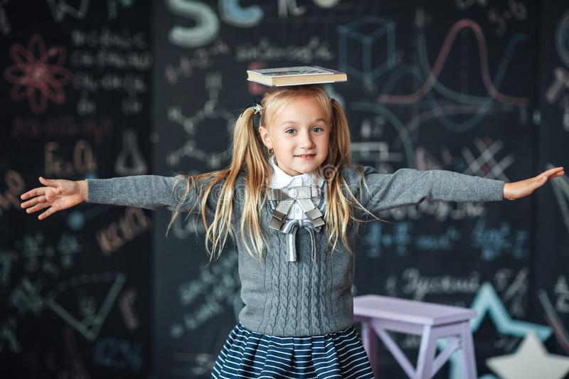 Back to school. little blond girl in school uniform child from elementary school keeps a books on her head. education. child with royalty free stock images