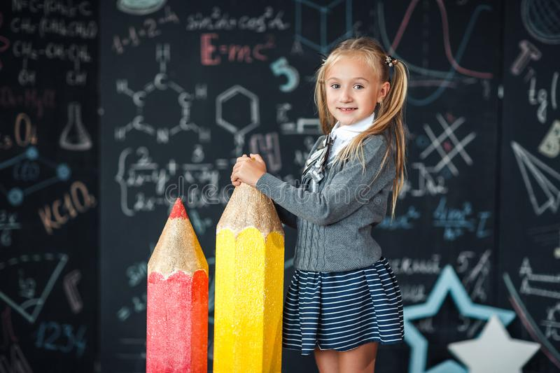 Back to school! A little blonde girl in school uniform stands with two very large red and yellow pencils on the floore against stock photos