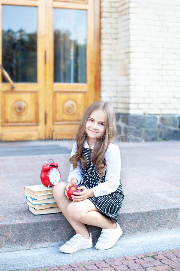 Back to school. Little girl schoolgirl sits on the steps near the school and holds an apple in her hands for lunch. Education and. School concept. Preschool royalty free stock image