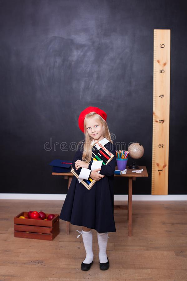 Back to school! Little girl schoolgirl stands with bills and learns to count. School concept. Pupil answers at lesson. The kid is royalty free stock image