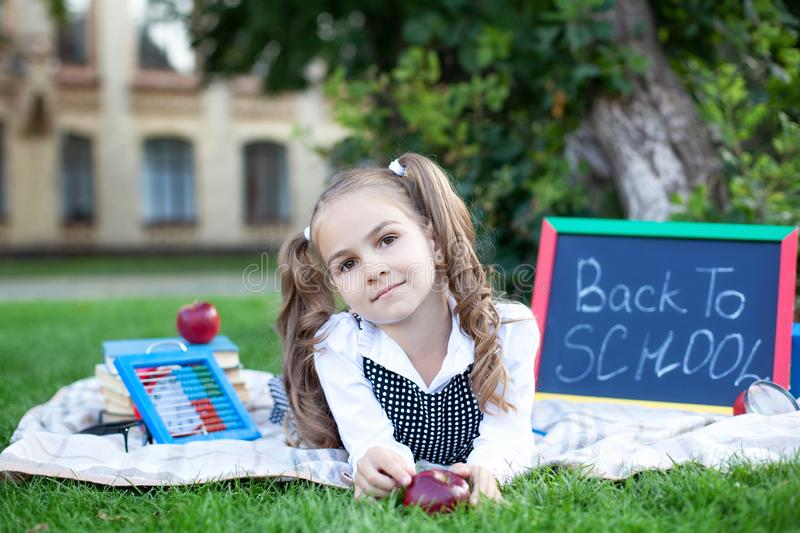 Back to school. little schoolgirl with lunch, books and pencils lies on the grass against the background of the school. Education stock photography
