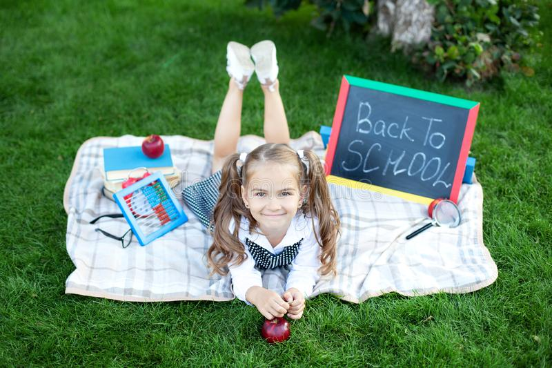 Back to school. little schoolgirl with lunch, books and pencils lies on the grass against the background of the school. Education royalty free stock images
