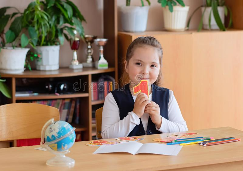 Back to school. Little schoolgirl sits at her desk and holds the number 1 in her hands stock photos
