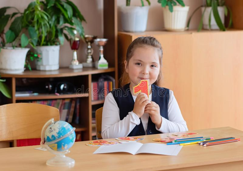Back to school. Little schoolgirl sits at her desk and holds the number 1 in her hands stock image