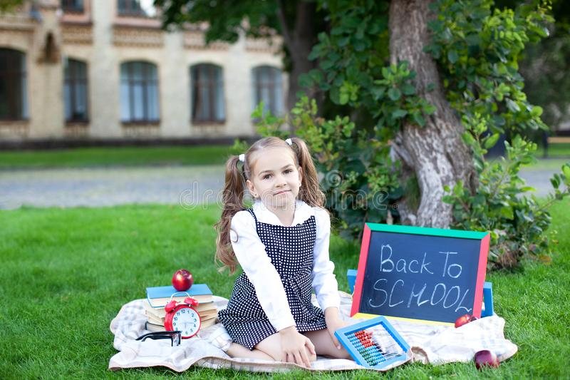 Back to school. little schoolgirl is sitting in the grass near a school with a school office. Education. Preschool education. Prim. Ary school student. Start of royalty free stock photos