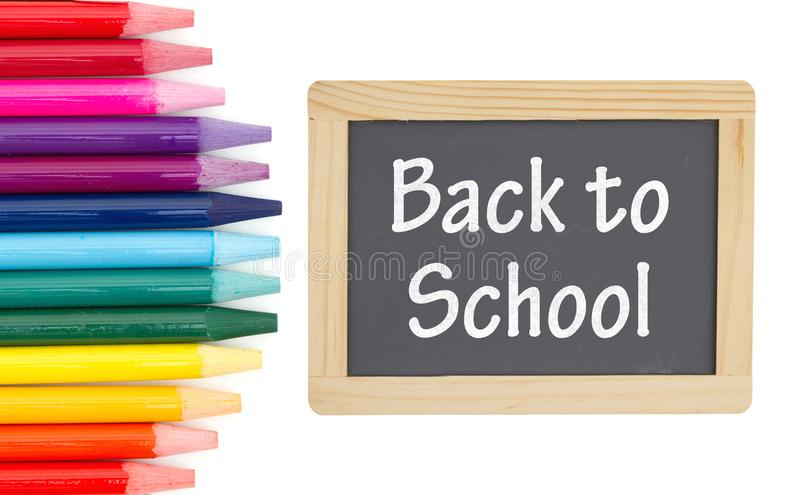 Back to School message on a chalkboard with colored watercolor pencils. Over white stock illustration