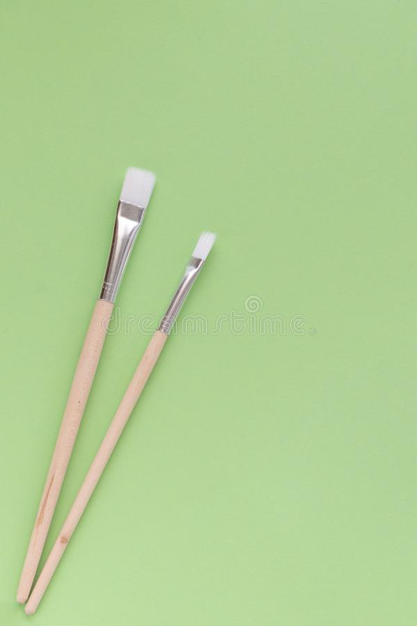 Back to school, minimalism concept. School supplies. Brushes for painting on pastel trendy green color paper background. Copy royalty free stock images