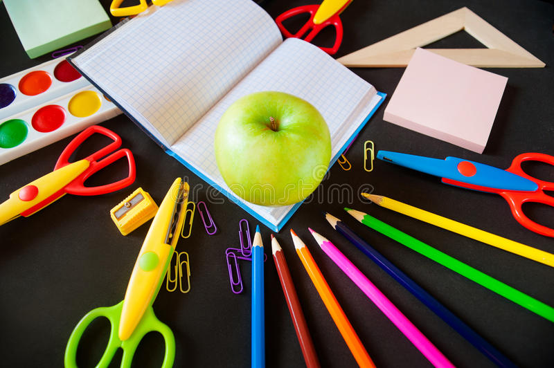 Back to school. Notepad with apple and supplies stock images
