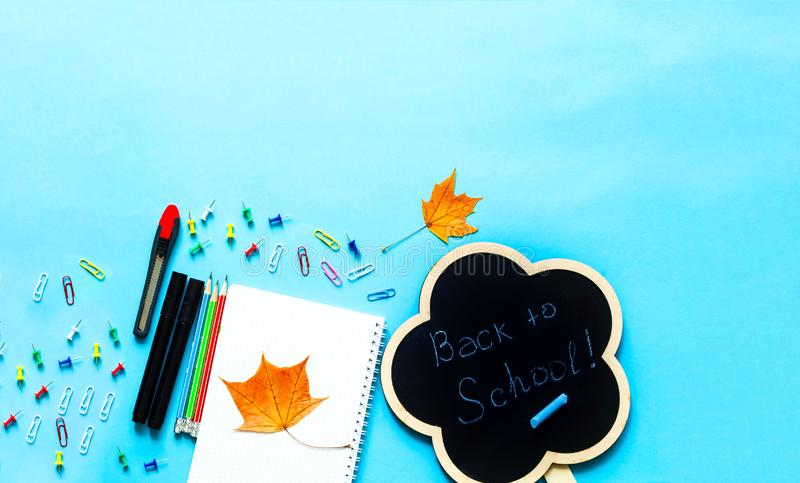 Back to school over chalkboard background. School supplies on blue background. Close-up, copy space royalty free stock photos
