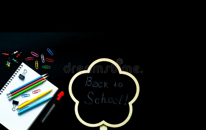 Back to school over chalkboard background. School supplies on black background stock photo