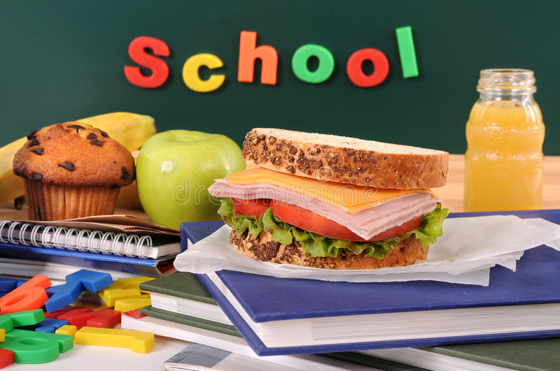 Back to school with packed lunch, sandwich, apple, drink on classroom desk or table royalty free stock image
