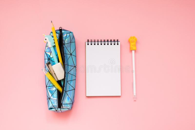 Back to school. Pencil case with school supplies on pink table stock photography