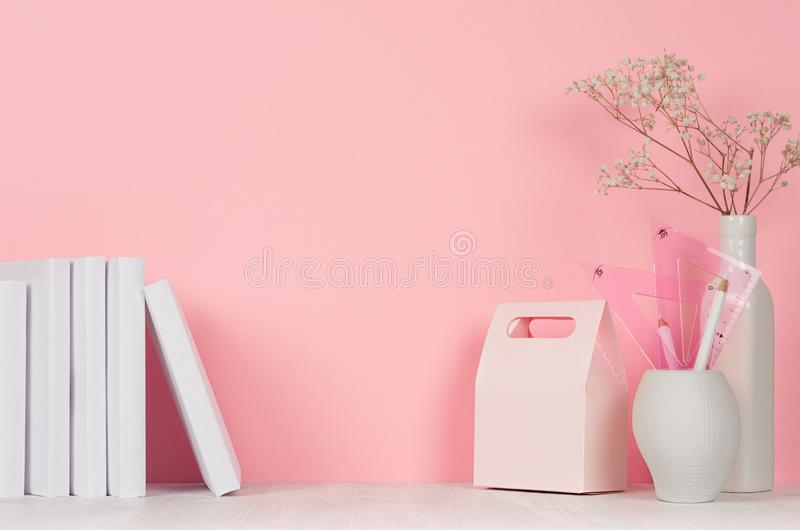 Back to school pink girl`s background - white stationery, books and lunch box on white wood table and pastel pink wall. stock image