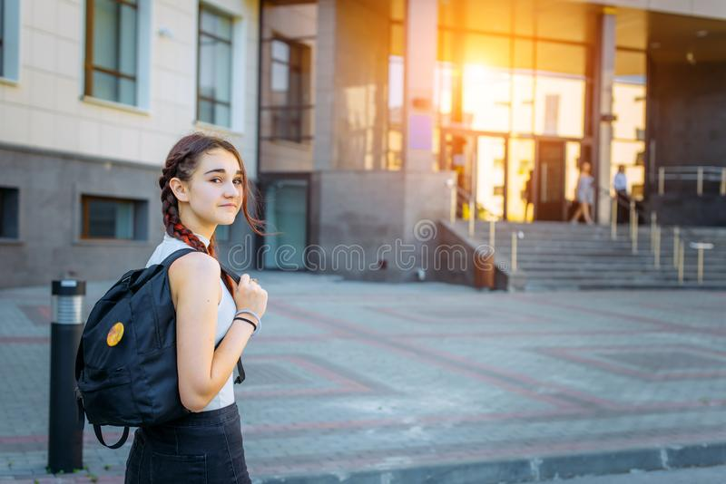 Back to school-portrait of a beautiful young schoolgirl with a backpack and long braids, education concept stock images