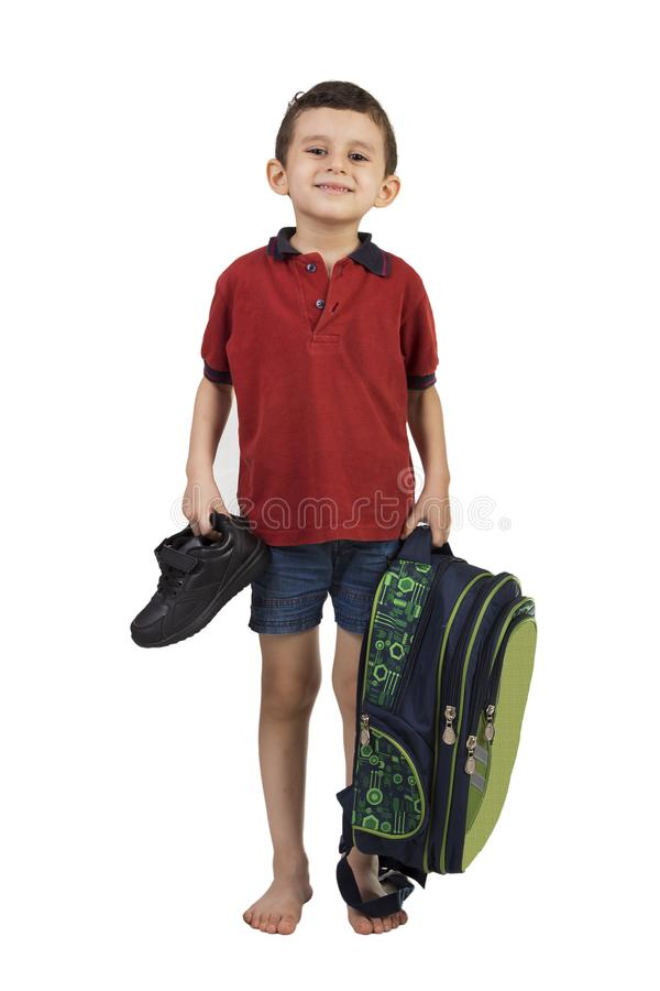 Back to school - Portrait of school boy child smiling and holding school bag and shoes stock photography