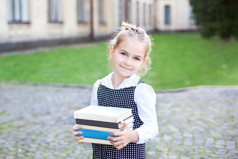 Back to school. Portrait of a schoolgirl with books, textbooks on the background of the school. Education concept. Preschool educa. Tion. Little girl reading a royalty free stock photo