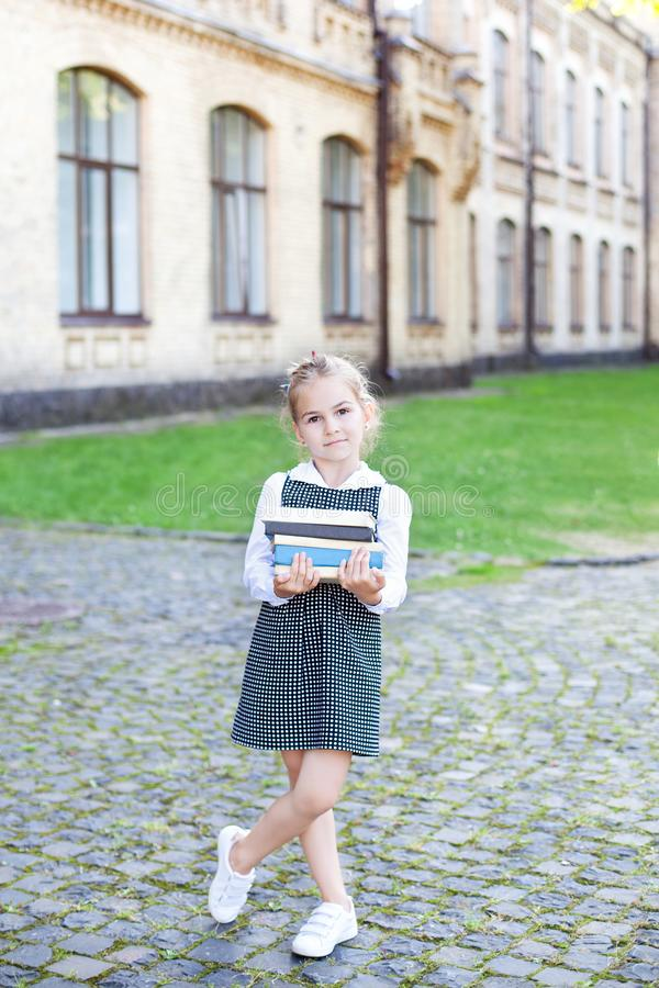 Back to school. Portrait of a schoolgirl with books, textbooks on the background of the school. Education concept. Preschool educa. Tion. Little girl reading a stock photography
